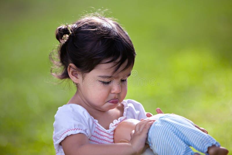 Kleines Mädchen draußen mit Puppe stockfotos