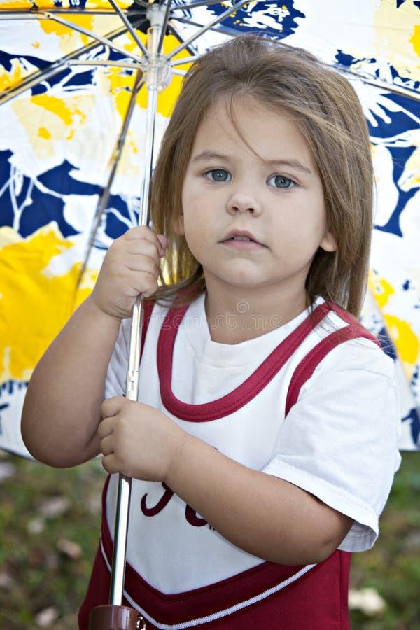 Kleines Mädchen draußen mit Regenschirm stockfoto