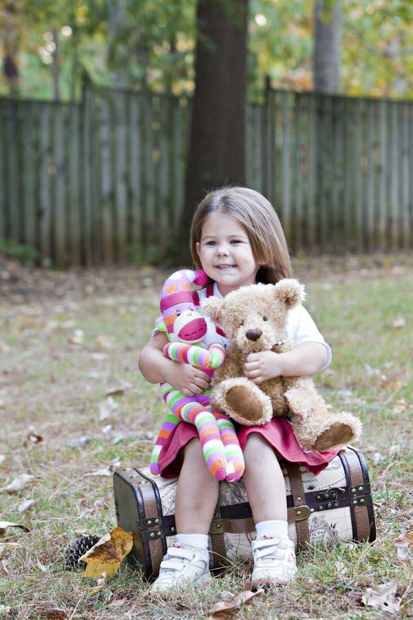 Kleines Mädchen draußen mit Spielzeugfallhammer und -bären stockfotografie