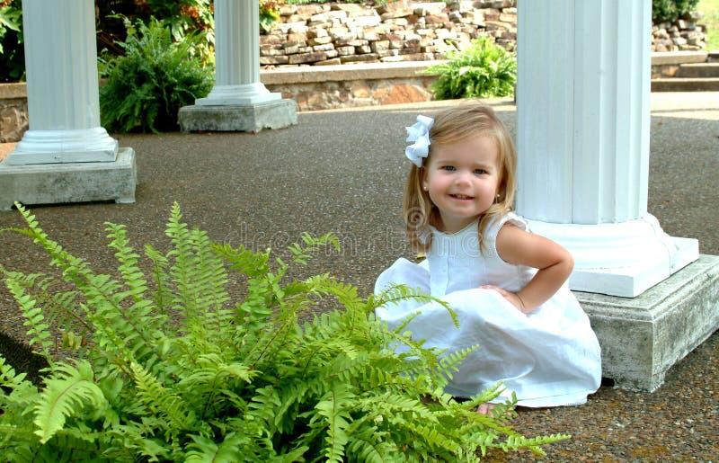 Kleines Mädchen durch die Spalten lizenzfreies stockfoto