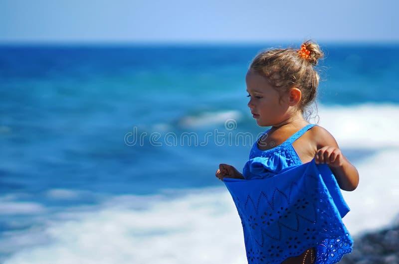 Kleines Mädchen in einem blauen Kleid, das auf dem Paradisos-Strand in Santorini spielt lizenzfreie stockfotos