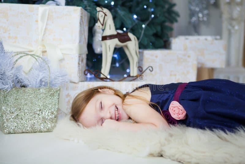 Kleines Mädchen in einem eleganten Kleid liegt und lacht über den Weihnachtsbaum lizenzfreie stockbilder