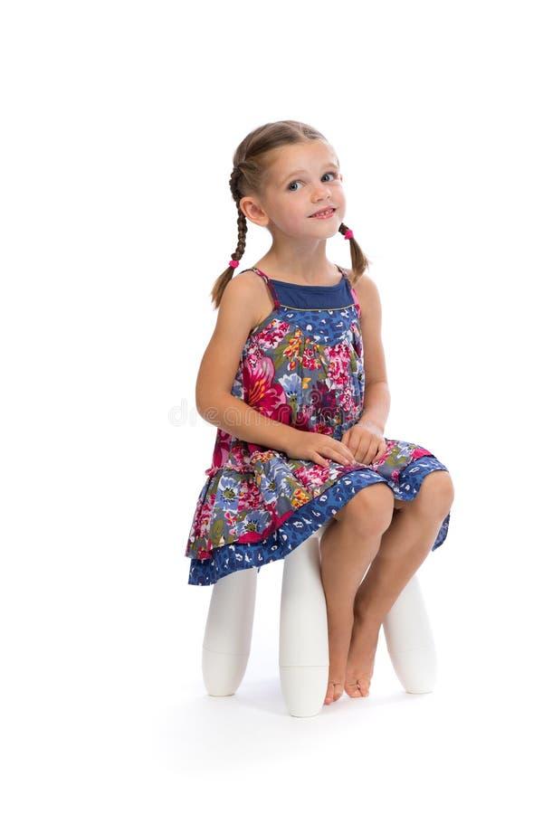 Kleines Mädchen in einem farbigen Kleid auf einem Stuhl im Studio und werfen lizenzfreies stockfoto
