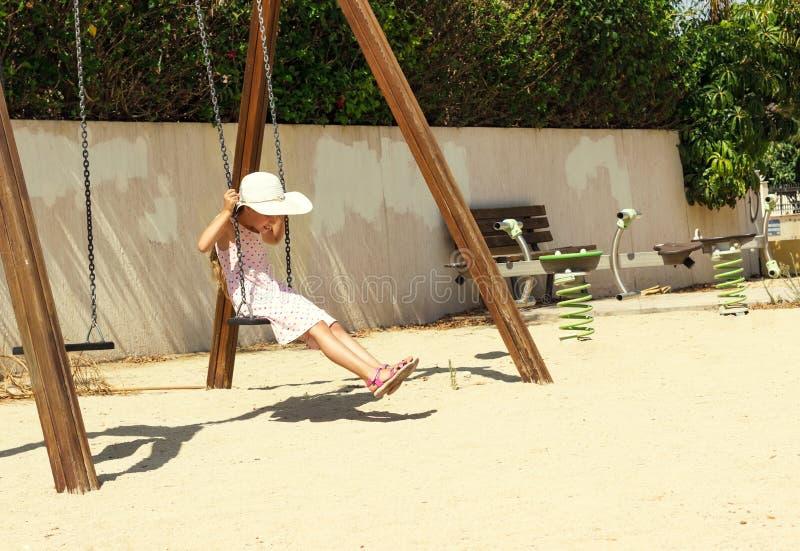 Kleines Mädchen in einem großen weißen Hut, der Spaß auf einem Schwingen am sonnigen Tag hat stockfotografie