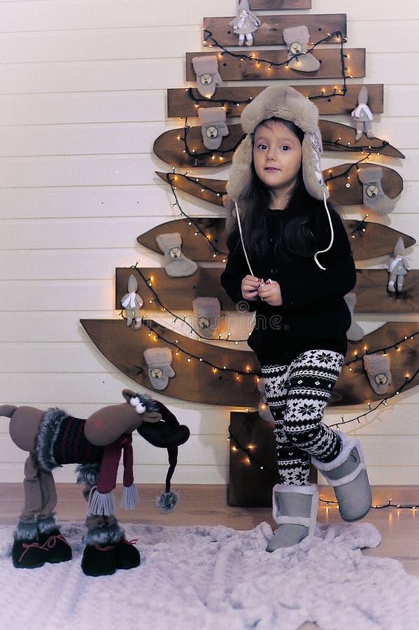 Kleines Mädchen in einem Kappen- und Spielzeugren Weihnachten lizenzfreies stockbild