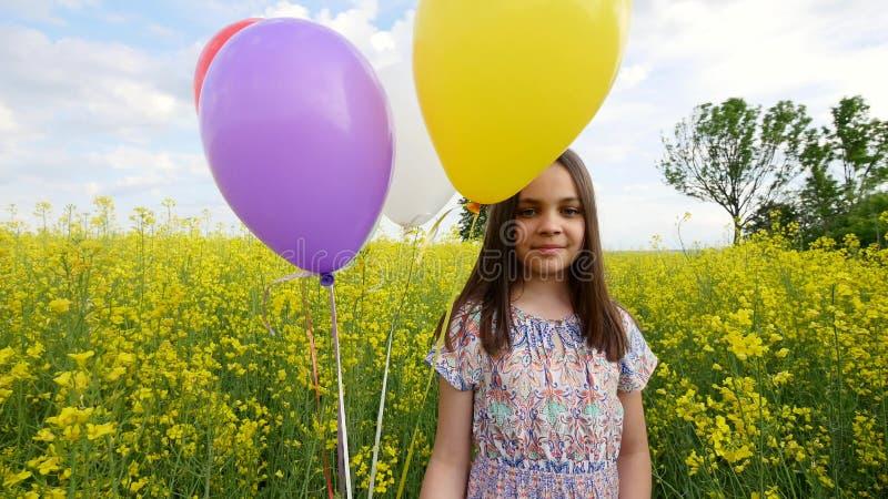 Kleines Mädchen in einem Kleid, das in der Hand durch gelbes Weizenfeld mit Ballonen läuft Zeitlupen lizenzfreie stockfotografie