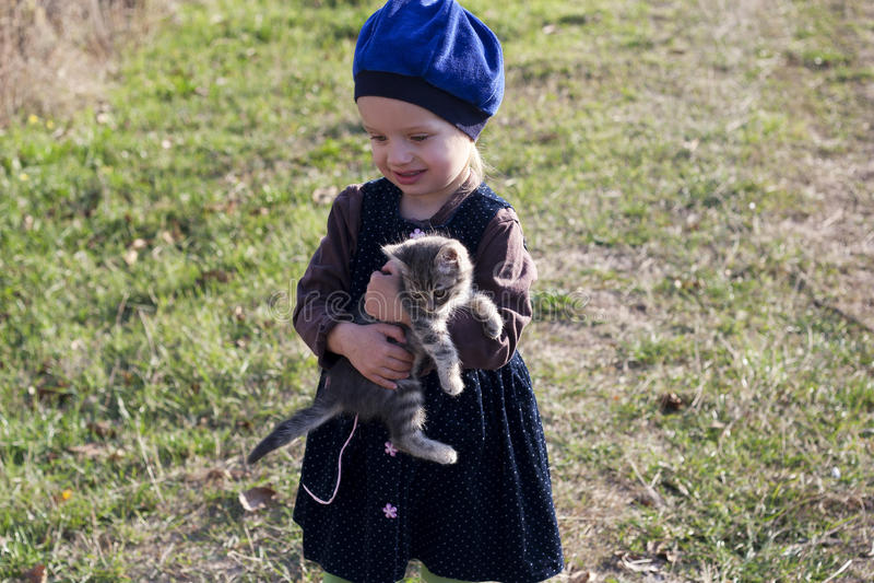 Kleines Mädchen in einem Kleid und in einem Barett mit einem grauen Kätzchen in der Hand stockfotografie