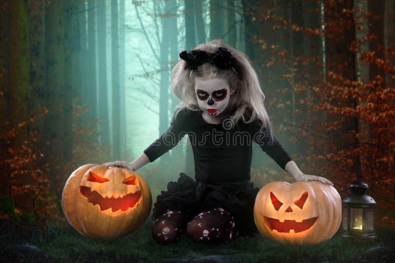 Kleines Mädchen in einem Kostüm der Hexe aufwerfend mit Kürbisen über feenhaftem Hintergrund Halloween stockfotos
