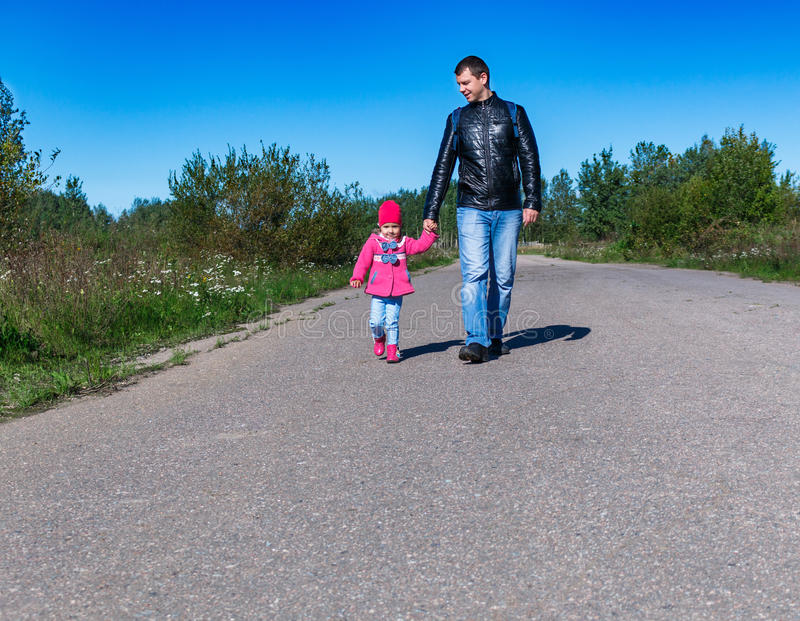 Kleines Mädchen in einem rosa Mantel gehend der Park sie die Hand des hohen gutaussehenden Mannes halten Tochter und Vati stockfoto