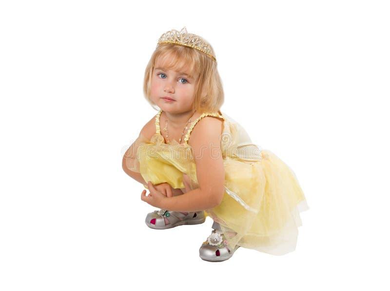 Kleines Mädchen in einem schönen gelben Kleid und in einer Krone auf Weißrückseite stockfoto