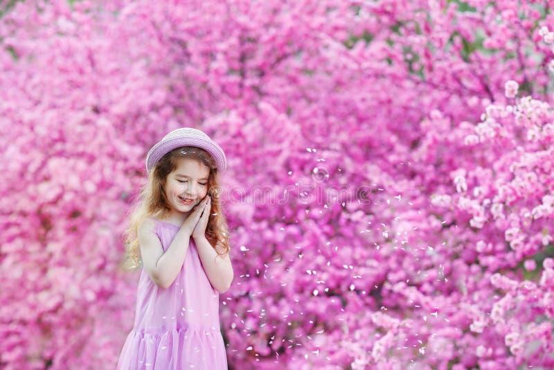 Kleines Mädchen in einem Strohhut betrachtet träumerisch die blühenden rosa Büsche von Kirschblüte lizenzfreie stockfotos