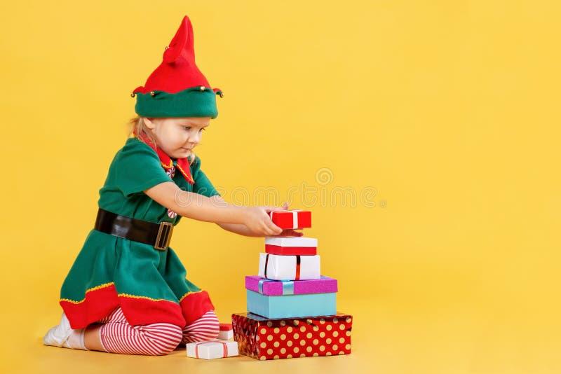 Kleines Mädchen in einem Weihnachtselfenkostüm auf einem gelben Hintergrund Das Kind errichtet eine Pyramide von Geschenkboxen Na lizenzfreie stockfotografie