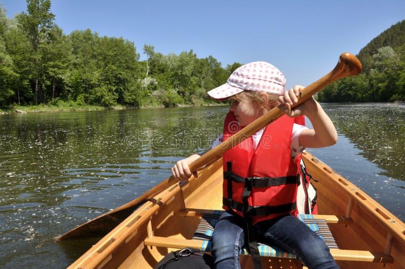 Kleines Mädchen in einer Schwimmweste in einem Kanu stockbild