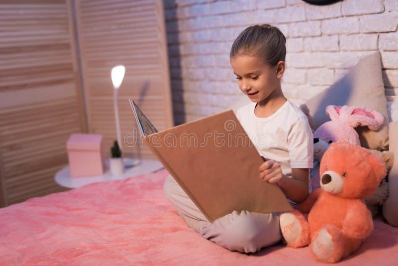 Kleines Mädchen, Enkelin ist Lesebuch nachts zu Hause lizenzfreie stockfotos