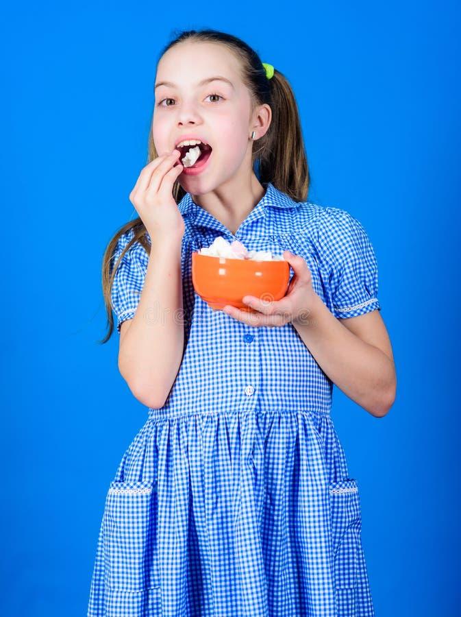 Kleines Mädchen essen Eibisch Nähren und Kalorie Schleckermaulkonzept glückliche kleines Kinderliebesbonbons und -festlichkeiten  lizenzfreie stockbilder