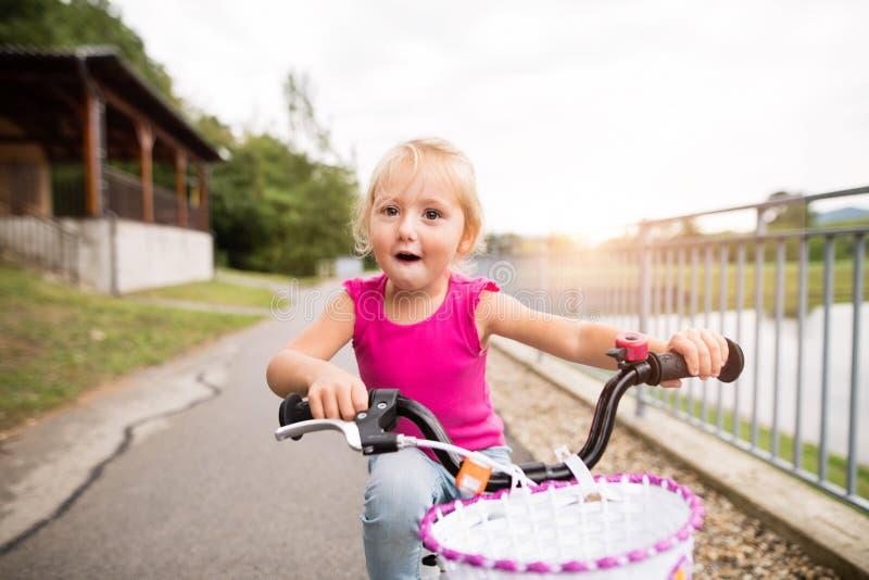 Kleines Mädchen fährt in die Natur durch den See rad lizenzfreie stockfotos