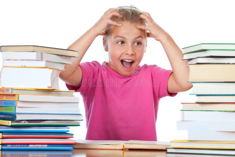 kleines Mädchen frustated zwischen vielen Büchern   stockfotografie
