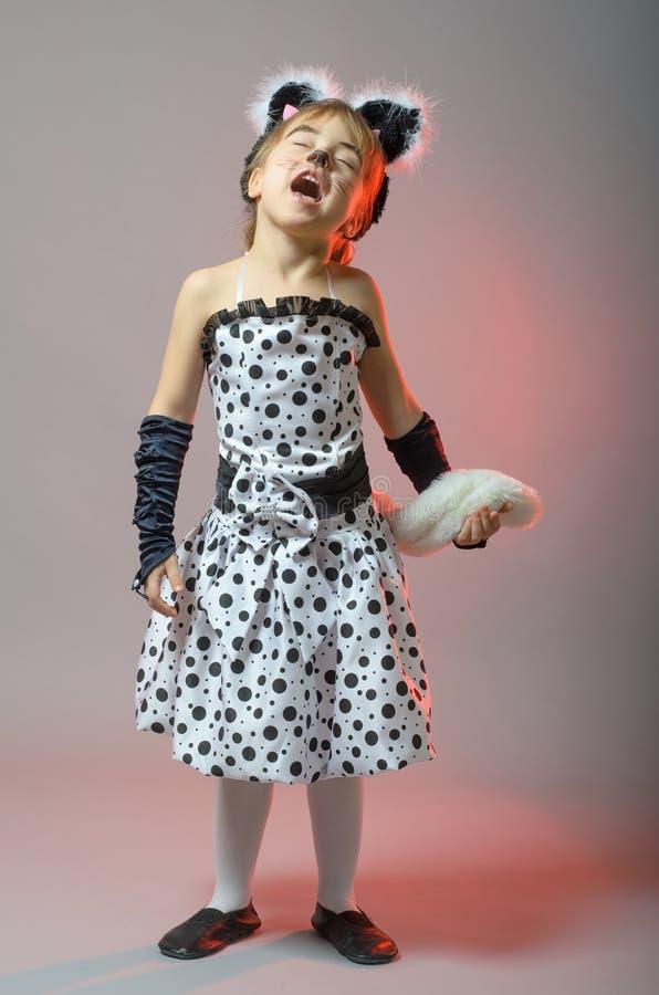 Kleines Mädchen gekleidet als Katze auf einem grauen Hintergrund stockbild
