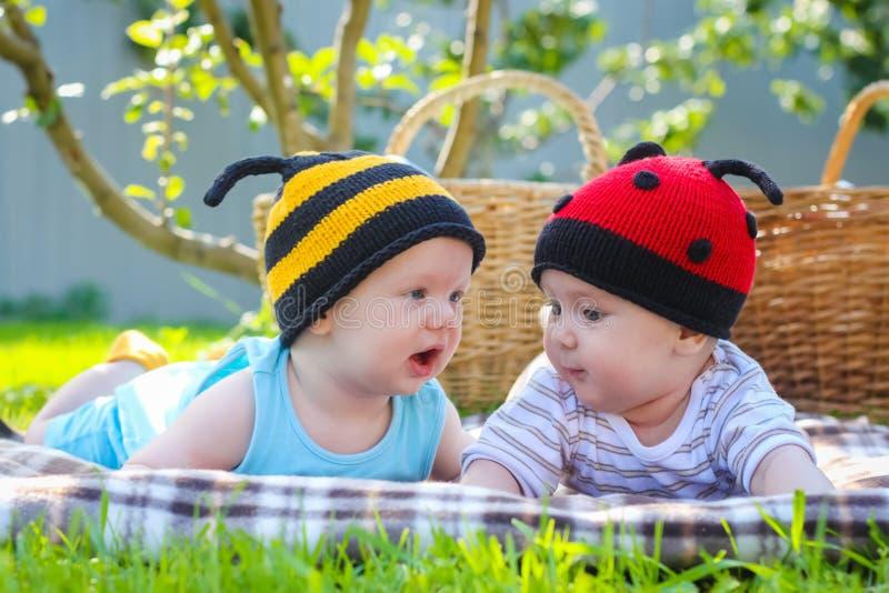 Kleines Mädchen in gestricktem Marienkäferhut und Junge, die draußen spielen, beste Freunde, glückliches Familien-, Liebes- und G stockfotografie