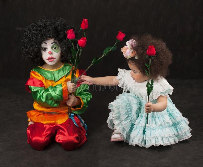 Kleines Mädchen gibt dem Jungen - der Clown Blumen, afrikanisch lizenzfreie stockbilder
