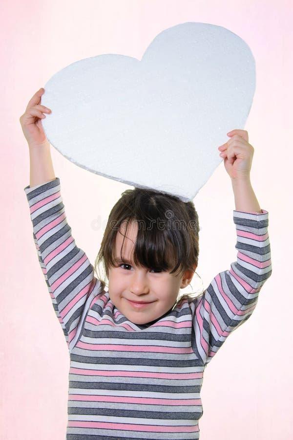 Kleines Mädchen hält ein Herz in seinen Händen stockfotografie