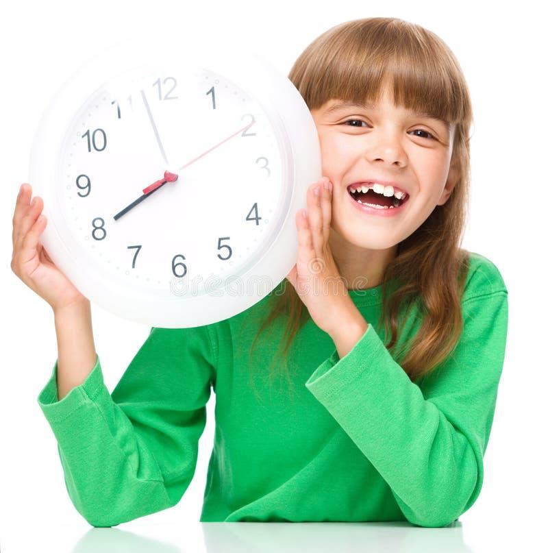 Kleines Mädchen hält große Uhr lizenzfreies stockfoto