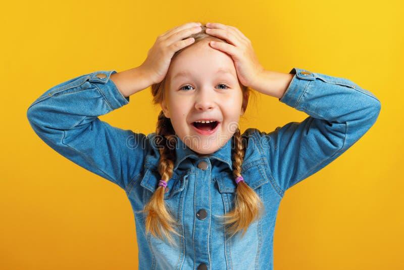 Kleines Mädchen hält Hände hinter ihrem Kopf auf gelbem Hintergrund Das Kind ist erstaunt, überrascht, emotional lizenzfreie stockfotos