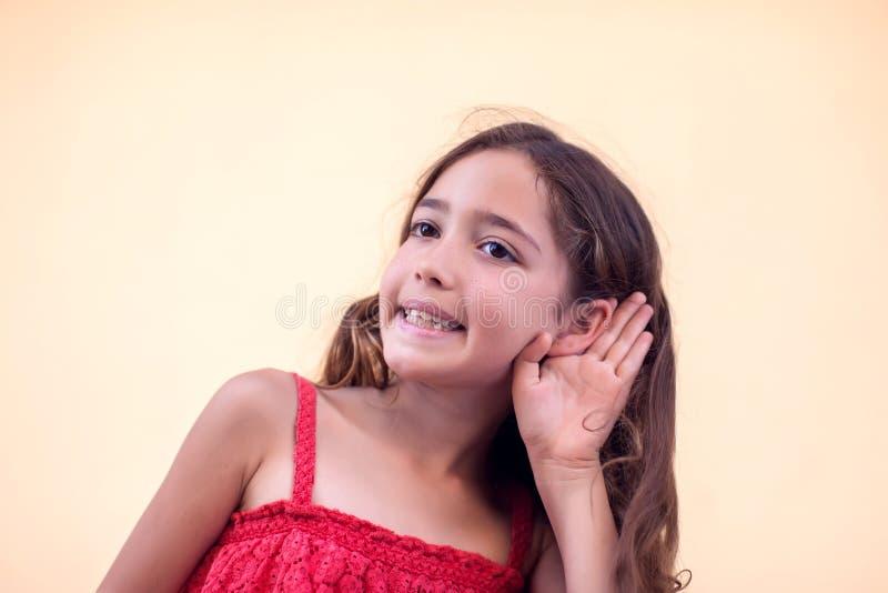 Kleines Mädchen hält Hand in Ohr und lächelt Konzept für Kinder und Emotionen lizenzfreies stockfoto