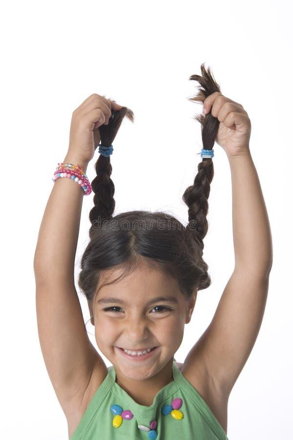 Kleines Mädchen hält ihre Zöpfe hoch für Spaß an lizenzfreie stockfotos