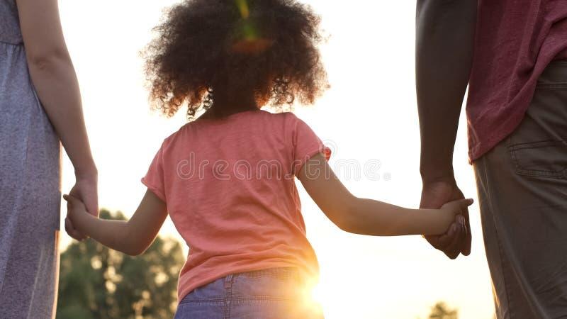 Kleines Mädchen hält Vater- und Mutterhände, Glück und Wohl in der Familie lizenzfreie stockfotografie