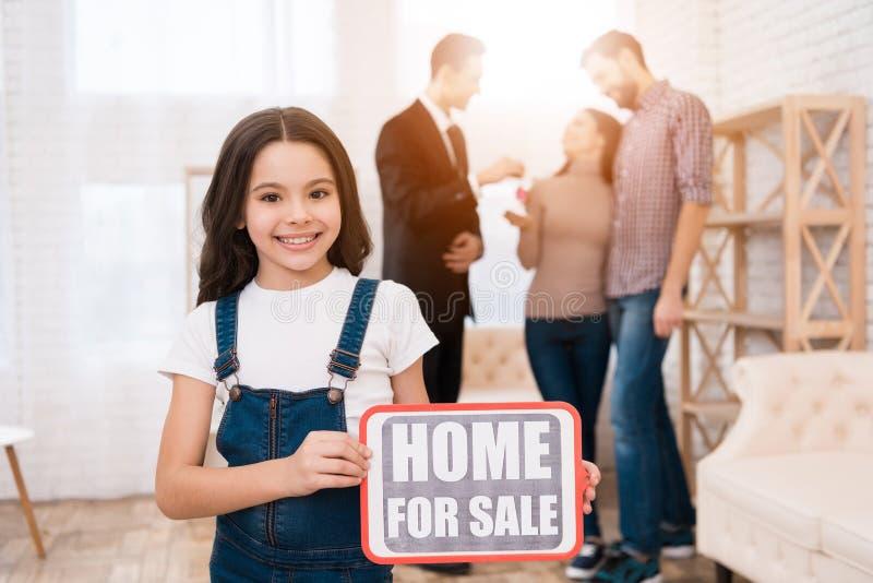 Kleines Mädchen hält Zeichen mit Aufschrift Haus für Verkauf Grundstücksmakler zeigt Wohnung zu den Paaren stockfoto
