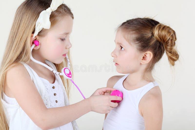 Kleines Mädchen hört Herzschlag eines anderen Mädchens durch Spielzeug phonendoscope stockfoto