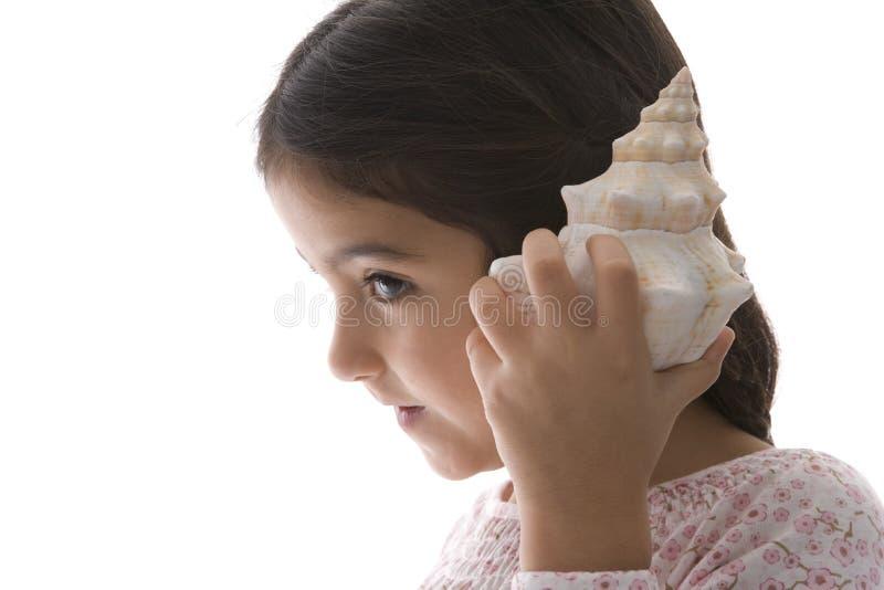 Kleines Mädchen hört zu einem großen Seeshell lizenzfreies stockbild