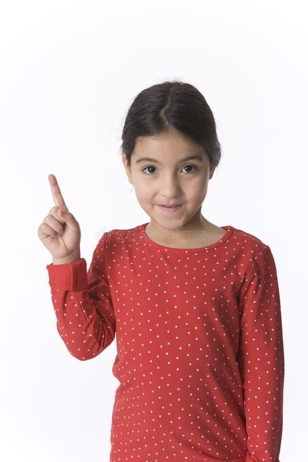 Kleines Mädchen hebt ihren Finger mit einem schüchternen Expr an lizenzfreies stockfoto
