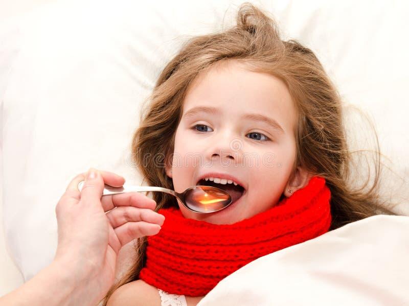 Kleines Mädchen im Bett, das Medizin mit Löffel einnimmt stockbilder