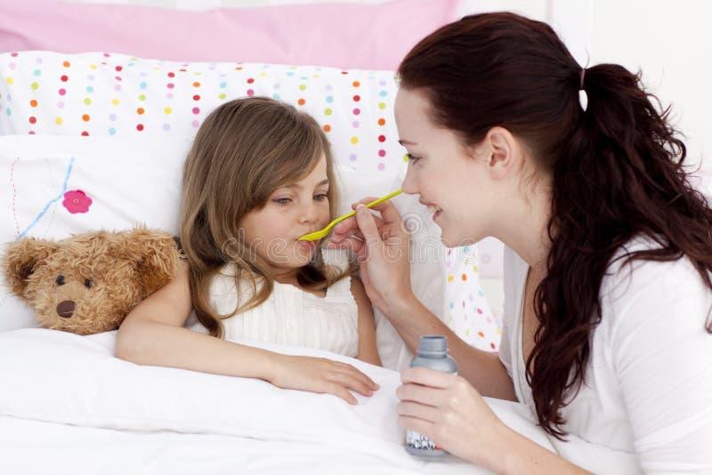 Kleines Mädchen im Bett, das Sirup nimmt lizenzfreies stockbild