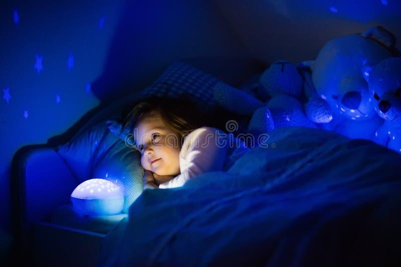 Kleines Mädchen im Bett mit Nachtlampe lizenzfreie stockfotos