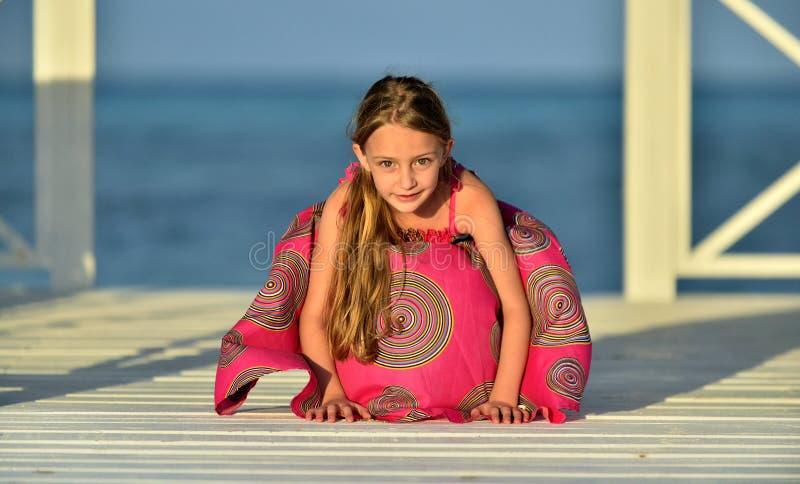 Kleines Mädchen im bunten Kleid auf dem hölzernen Pier nahe dem Ozean stockfotografie