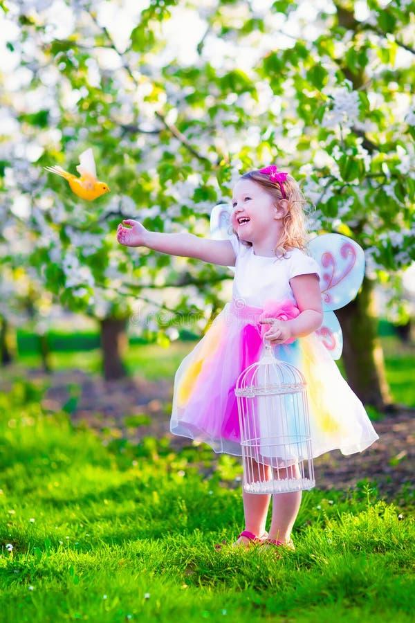 Kleines Mädchen im feenhaften Kostüm, das einen Vogel einzieht stockfotos