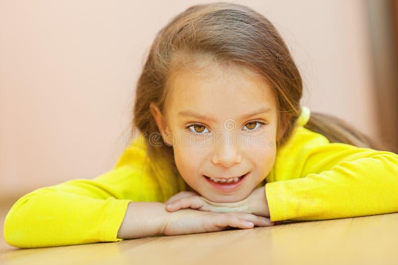Kleines Mädchen im gelben Kleidlügen lizenzfreie stockfotografie