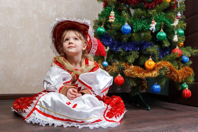 Kleines Mädchen im Karnevalskostüm sitzen nahe Weihnachtsbaum stockfotos