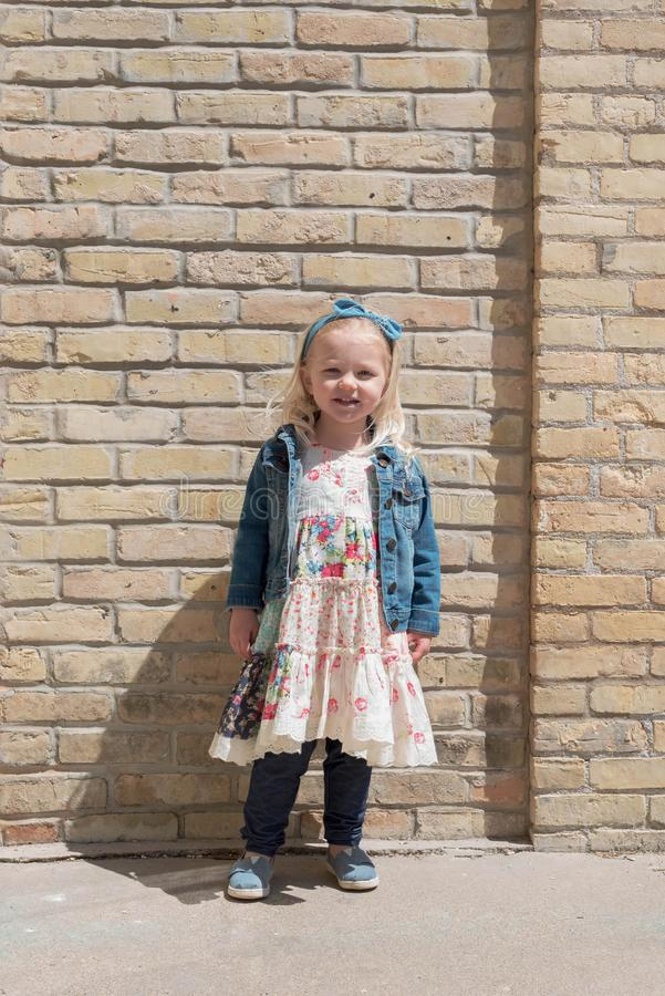 Kleines Mädchen im Kleid, das vor Backsteinmauer steht lizenzfreie stockbilder