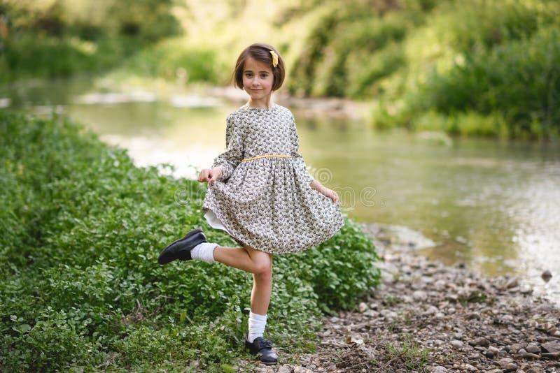 Kleines Mädchen im Naturstrom, der schönes Kleid trägt stockbilder