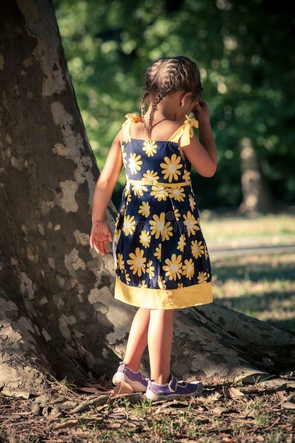 Kleines Mädchen im netten Sommerkleiderweg im Park durch enormen Baum lizenzfreie stockbilder