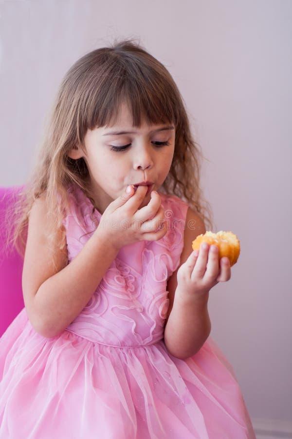 Kleines Mädchen im rosa Abendkleid, süßen kleinen Kuchen essend stockbilder