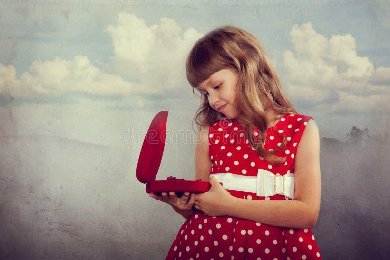 Kleines Mädchen im roten Kleid, das ihr Geschenk hält stockfotos
