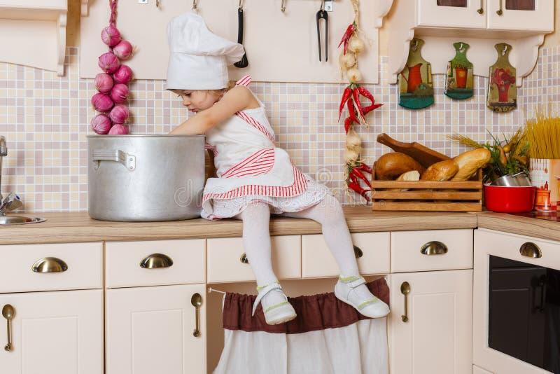 Kleines Mädchen im Schutzblech in der Küche. stockbilder