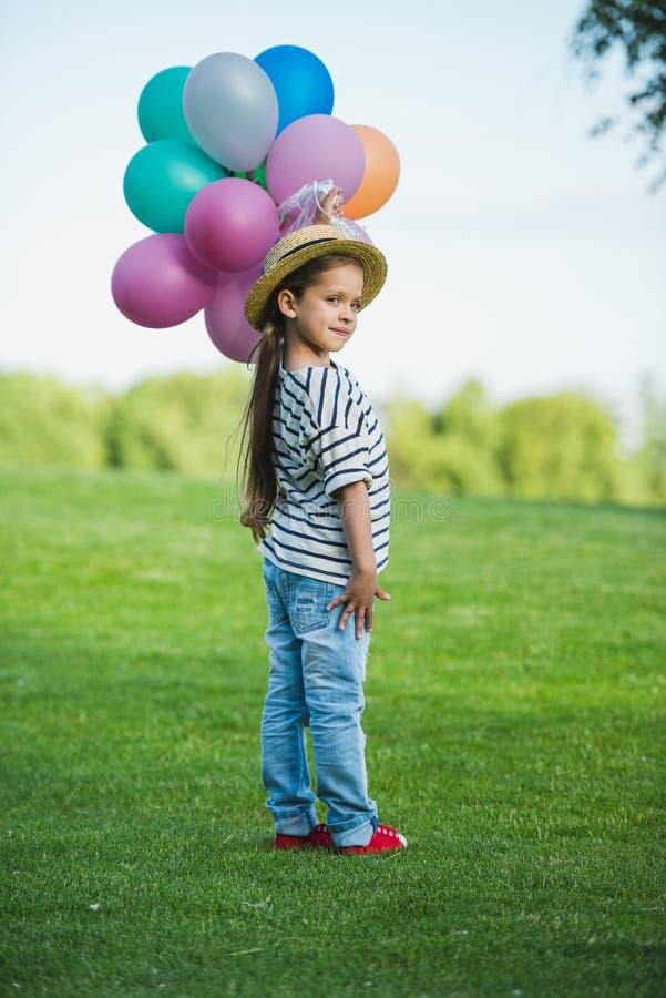 Kleines Mädchen im Strohhut, der Bündel bunte Ballone bei der Stellung im Park hält stockfotos