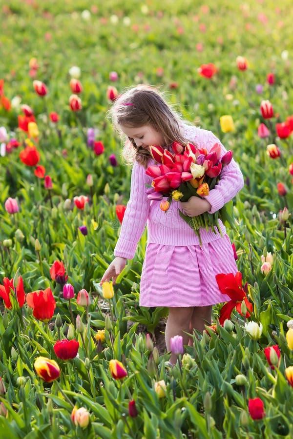 Kleines Mädchen im Tulpenblumengarten stockfotografie