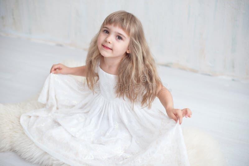 Kleines Mädchen im weißen breiten Kleid, das auf dem Boden sitzt stockbild